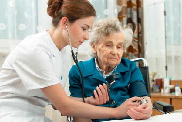 nurse doing a blood pressure check of an elder woman