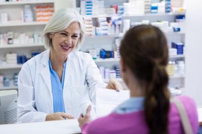 Pharmacist giving prescriptions of medicine to customer in pharmacy